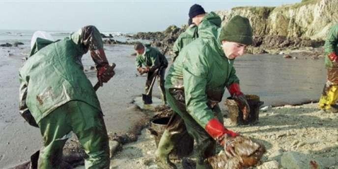 Des militaires du 503ème régiment du train, de Bordeaux, s'affairent, le 26 janvier 2000 à Batz-sur-Mer, au nettoyage d'une crique encore entièrement recouverte par une nappe de mazout provenant du pétrolier Erika.