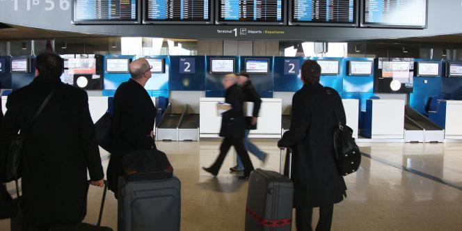 Des passagers regardent les horaires des avions à l'aéroport de Roissy-Charles-de-Gaulle, le 18 décembre 2009.