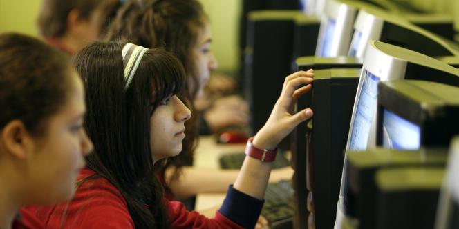 Collégiens en classe devant des ordinateurs.
