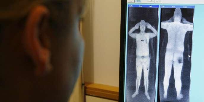 Un policier examine le scan d'un passager à l'aéroport de Manchester.