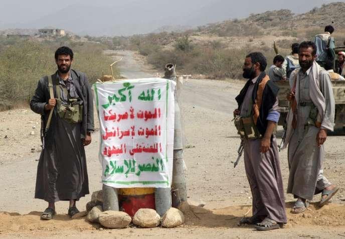 Des insurgés houthistes se tiennent à un point de contrôle à Saada, dans le nord-ouest du Yémen, le 16 février 2010.  Une banderole, en arabe, reprend leur slogan :