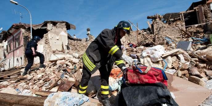 Des pompiers fouillent dans les ruines des bâtiments totalement détruits par le séisme qui a touché la région de l'Aquila, dans la nuit du 6 avril 2009.
