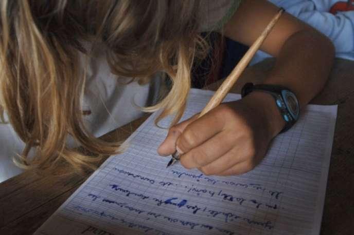 Un élève de CM2 écrit une dictée le 8 juin 2007 sous le préau de l'école primaire du Puits Picard, à Caen.