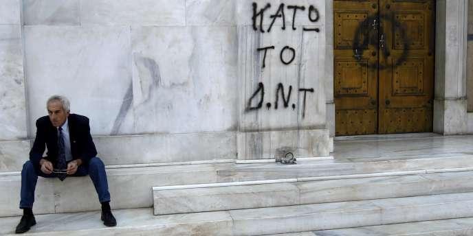 Un homme assis devant le siège de la Banque de Grèce, en mai 2010.