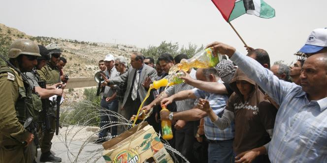 Des soldats israéliens font face à des manifestants palestiniens, qui vident des bouteilles de jus d'orange provenant de colonies israéliennes en Cisjordanie, dimanche 9 mai.