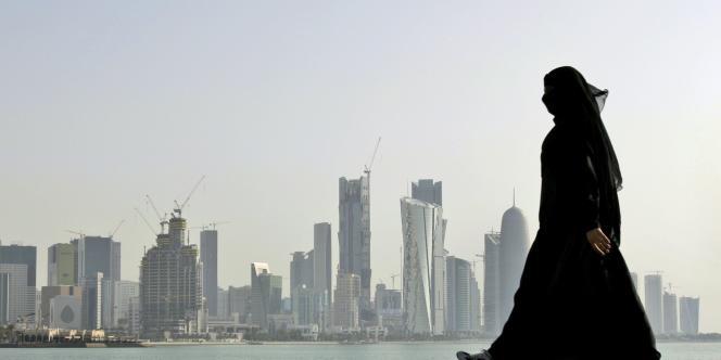 Une femme marche devant la baie (qui comporte une corniche de 7 km de long) face à Doha, ville située située sur le golfe Persique.