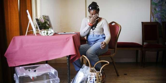 Une jeune femme essuie une larme le 21 mai à la mairie de Villiers-sur-Marne, où a été installé un cahier de condoléances en mémoire d'Aurélie Fouquet.