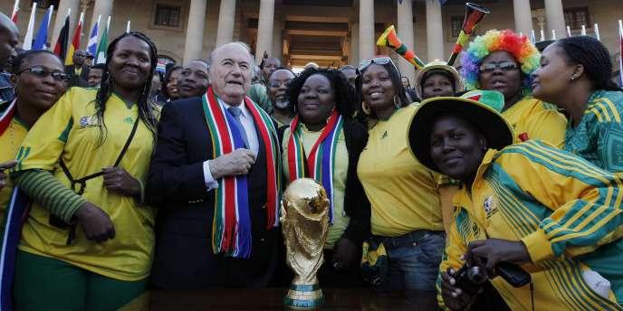 Le président de la FIFA, Joseph Blatter, apporte le trophée de la Coupe du monde au siège du gouvernement sud-africain, le 4 juin 2010 à Pretoria.
