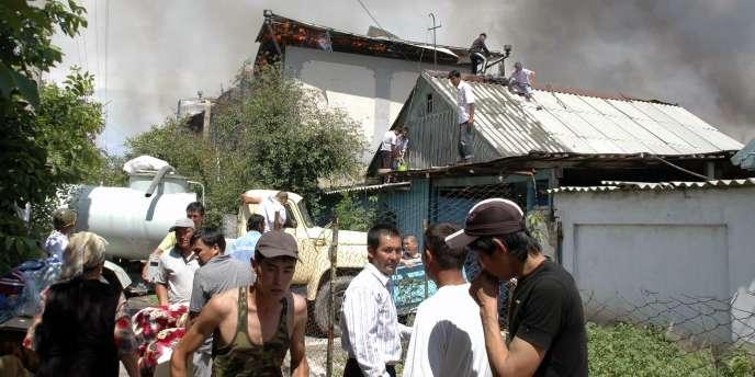Des Ouzbeks tentent d'éteindre l'incendie de leur maison, après l'attaque de Kirghizes, à Djelalabad.