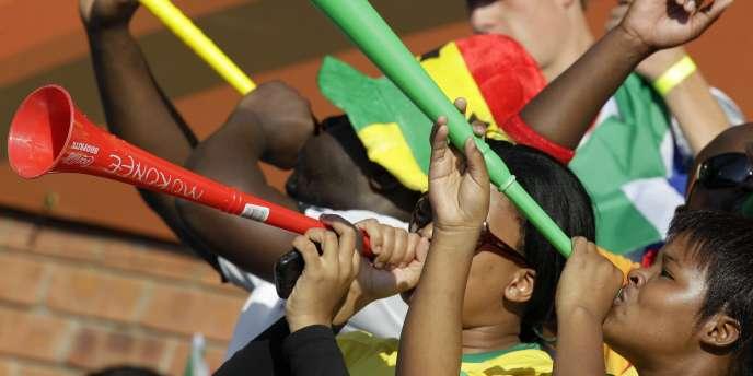 Des supporters soufflent dans leurs vuvuzelas, lors du match opposant la Serbie et le Ghana, le 13 juin.  Le bourdonnement incessant de ces trompettes en plastique lors des rencontres exaspère de nombreuses équipes et observateurs étrangers.