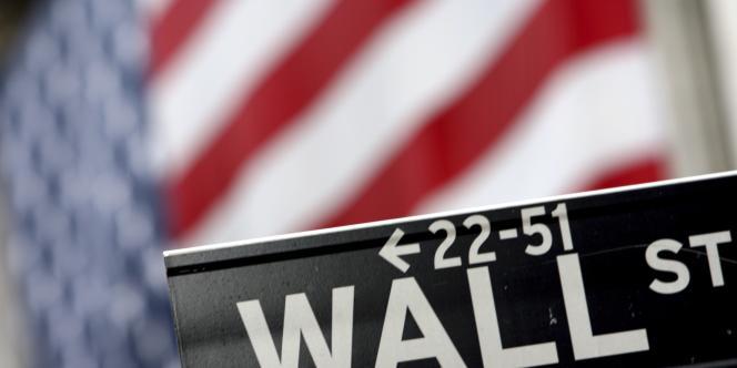 Vue d'un panneau signalant Wall Street devant le drapeau américain, à New York.