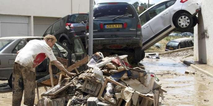 Un homme regroupe les déchets charriés par les eaux, à Draguignan, dans le Var, mercredi 16 juin.