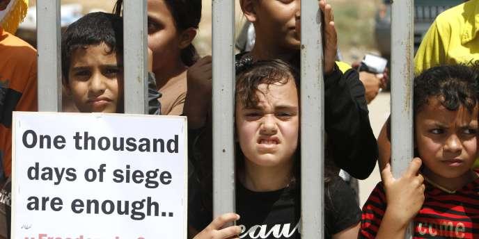 Des enfants palestiniens manifestent devant une zone industrielles pour la levée du blocus de la bande de Gaza, le 20 juin.