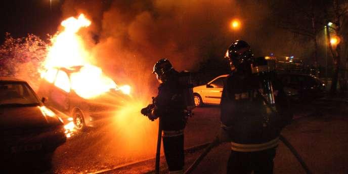 Des pompiers cherchant à éteindre l'incendie d'une voiture en 2008.