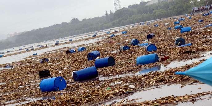 Des fûts contenant des produits chimiques emportés par les inondations dans la rivière Songhua à Jilin (Chine), le 28 juillet 2010.
