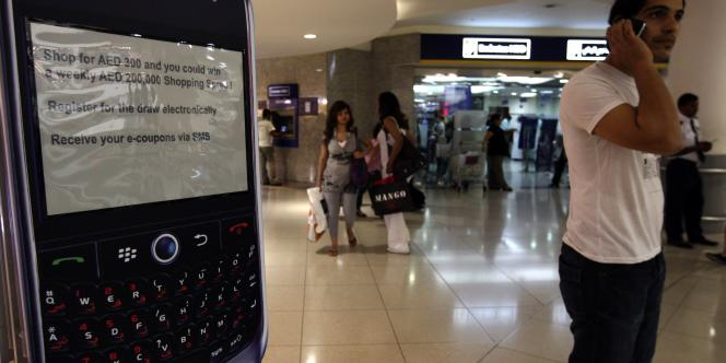 Un homme téléphone près d'un stand BlackBerry dans un centre commercial de Dubaï, le 1er août.