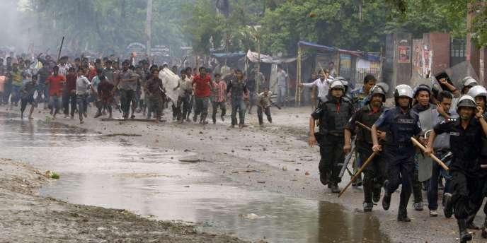 Des ouvriers et manifestants chargent la police dans la zone d'Ashulia, au nord-ouest de Dacca, la capitale du Bangladesh, le 2 août 2010.