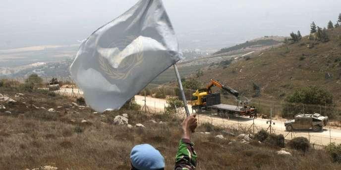 Un soldat de l'ONU agite son drapeau devant les soldats israéliens.