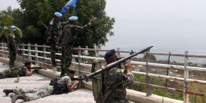 Des soldats libanais prennent positions tandis que des bérets bleus de l'ONU s'adressent aux soldats israéliens.