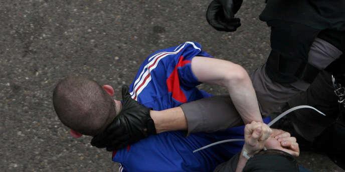 Un hooligan est arrêté aux abords d'un stade par les forces de police.