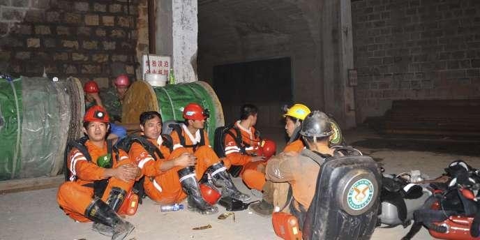 Des sauveteurs attendant à l'entrée de la mine d'or de Luoshan, en CHine où sept personnes sont encore prisonnières après un incendie.