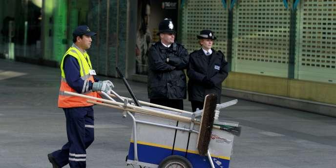Un balayeur passe devant deux policiers, devant la cathédrale de Westminster, samedi. Vendredi soir, Scotland Yard avait arrêté six hommes travaillant dans le nettoyage et suspectés de vouloir commettre un attentat lors de la visite de Benoît XVI à Londres.