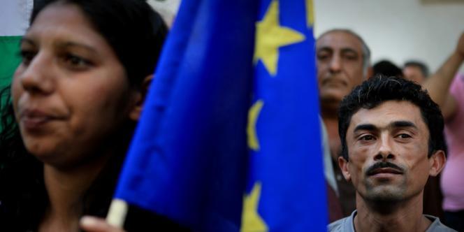 Des Roms de Bulgarie brandissent un drapeau européen lors d'une protestation contre la politique de démantèlement de camps en France.