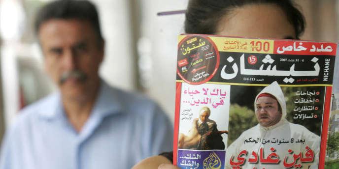 Un femme montre un exemplaire de l'hebdomadaire