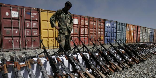 Un policier afghan face aux armes saisies auprès d'entreprises privées de de sécurité, le 5 octobre 2010, à Kaboul.