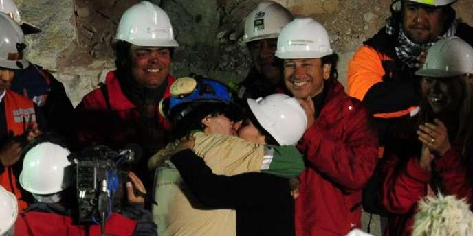 Osman Araya embrasse sa femme à sa sortie de la mine, mercredi. Sur les conseils de la NASA, des psychologues ont notamment préparé les mineurs aux difficultés qu'ils pourraient rencontrer pour retrouver une