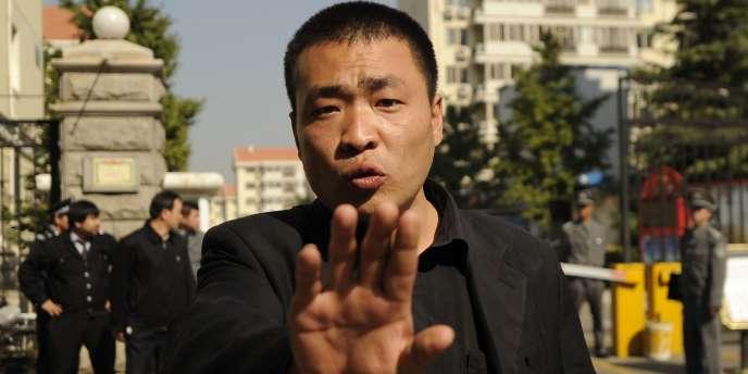 Un policier en civil essaie de repousser des photographes postés devant la résidence de Liu xia, la femme de Liu Xiaobo.