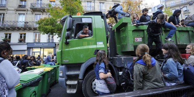 Des lycéens bloquent la rue et escaladent un camion devant le lycée Turgot, à Paris, le 15 octobre. Ils ont provoqué un gigantesque embouteillage au centre de la capitale.