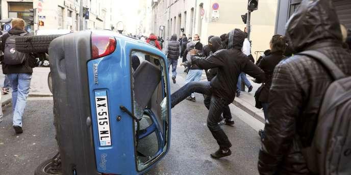 Un groupe de jeunes masqués s'en prend à une voiture, dans les rues de Lyon, jeudi 21 octobre.