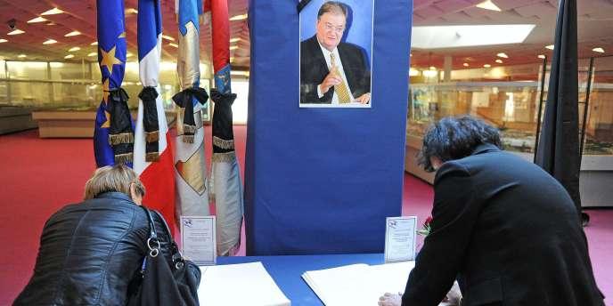 Des Montpelliérains signent un cahier de doléances devant le portrait de Georges Frêche, dans le hall d'entrée de la mairie de Montpellier.