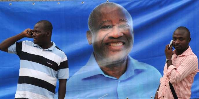 Des partisans de Laurent Gbabgo devant une banderole à son effigie, dans la capitale de la Côte d'Ivoire, Abidjan.