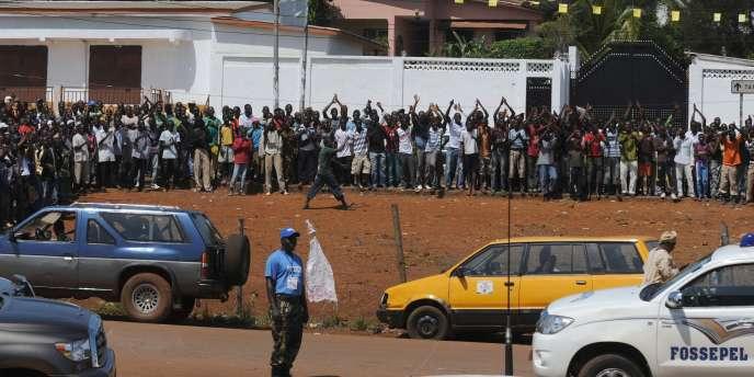 Des Guinéens attendent les résultats des élections devant un bureau de vote, à Motato, dans la banlieue de Conakry, mardi 9 novembre.