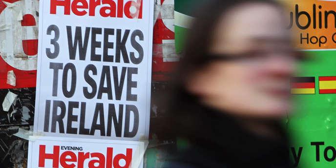 A Dublin, une passante devant les gros titres d'un quotidien en novembre 2010  :