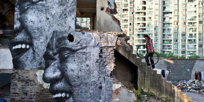 Photo prise sur le site de l'artiste JR montrant des portraits géants sur une maison délabrée à Shanghaï.