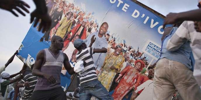 Des partisans d'Alassane Ouattara s'en prennent à une affiche de campagne de Laurent Gbagbo, le 2 décembre à Abidjan, après l'annonce par la Commission électorale de la victoire de leur candidat à la présidentielle.