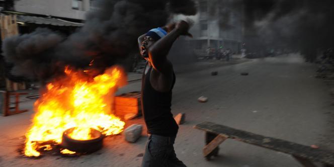 Des partisans d'Alassane Ouattara brûlent des pneus pour manifester leur mécontentement, vendredi à Abidjan.