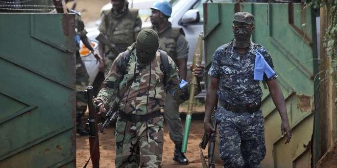 Des membres des Forces nouvelles sortent lourdement armés de l'hôtel qui sert de quartier général à Alassane Ouattara, jeudi 16 décembre.