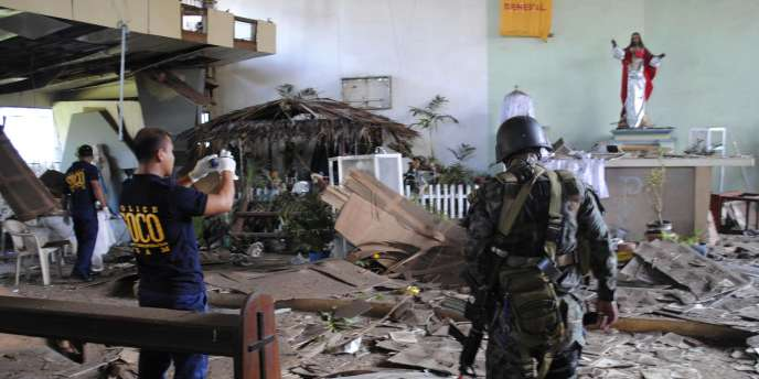 La police nationale philippine, sur les lieux de l'explosion d'une bombe lors de la messe de Noël d'une église d'une base policière de Jolo.