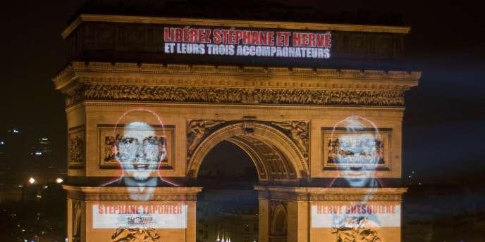 Les visages de Stéphane Taponier et Hervé Ghesquière projetés sur l'Arc de triomphe, mercredi 29 décembre.