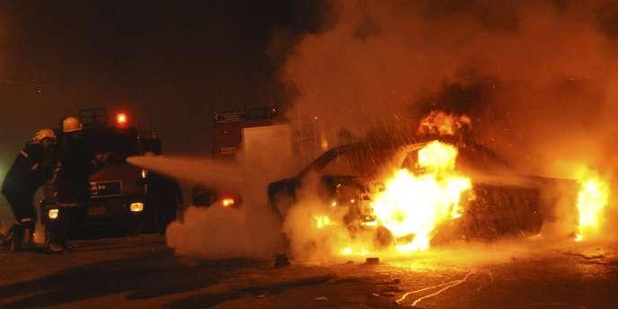 Des pompiers tentent d'éteindre la voiture qui a explosée peu après minuit devant une église d'Alexandrie.