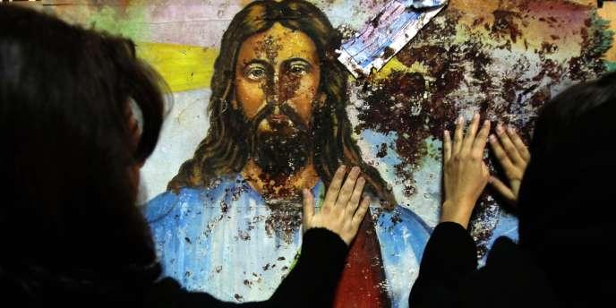 Des Egyptiens chrétiens touchent une représentation du Christ maculée de sang, dans l'église des Saints à Alexandrie.