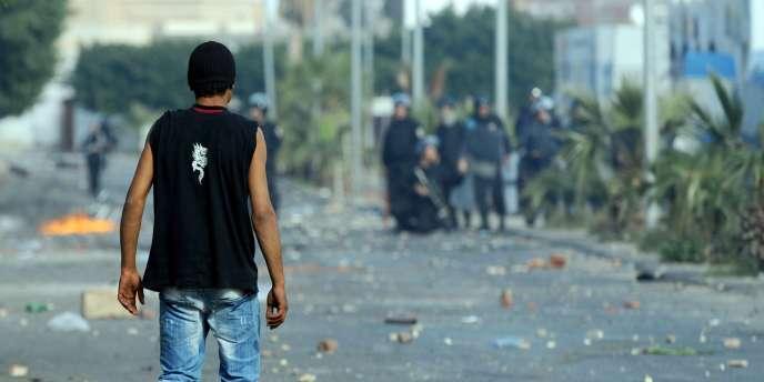 Un manifestant face à des policiers à Regueb, près de Sidi Bouzid, le 10 janvier 2011.