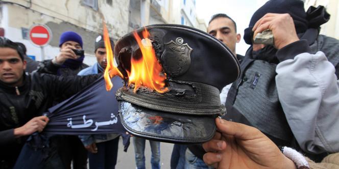 Des émeutiers brûlent une casquette de policier.