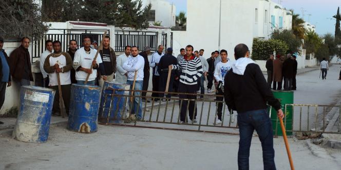 Des hommes armés de bâtons montent la garde à l'entrée de leur quartier pour éviter la venue de pillards.