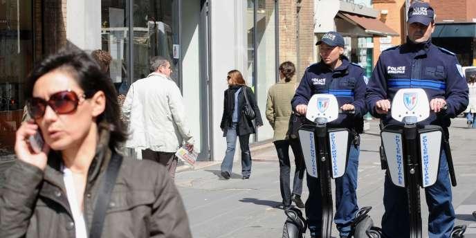 Une femme téléphone devant des policiers municipaux.