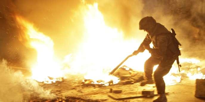 Un soldat libanais tente d'éteindre un incendie bloquant une route près de l'aéroport de Beyrouth, allumé en protestation contre le Hezbollah, le 24 janvier.